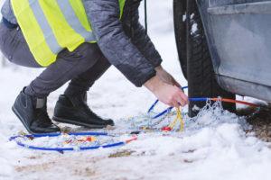 Schneeketten montieren mit Warnweste