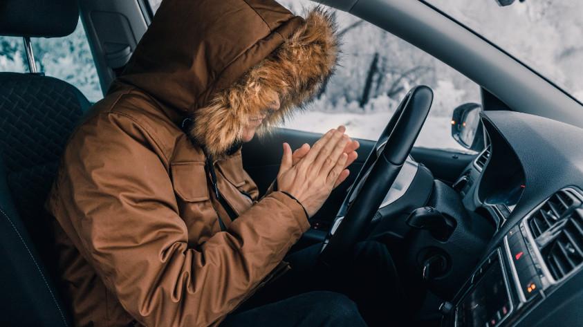 Mann friert mit Jacke im Auto